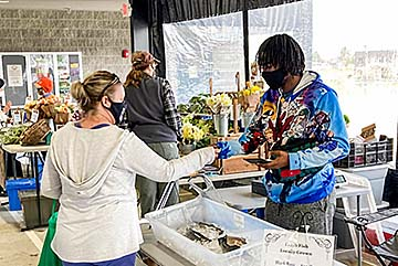A farmers market customer interacts with a Lincoln University representative at Lincoln's vendor stand.