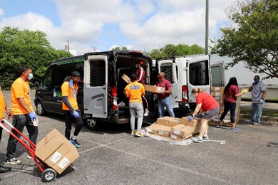 Individuals load boxes in the back of a van.