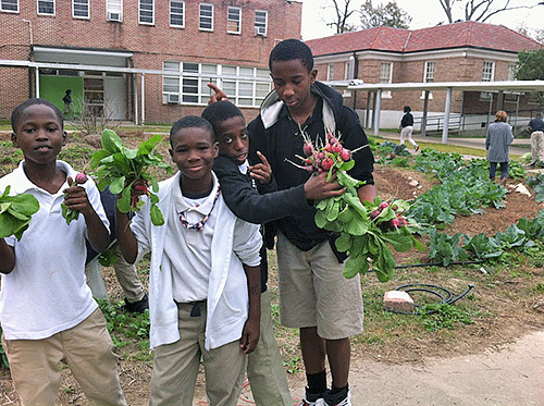 Photo courtesy of Stephanie Elwood. Thrive Academy students display the radishes they grew and picked from their campus garden as a part of the SU Ag Center's Fast Track Program.