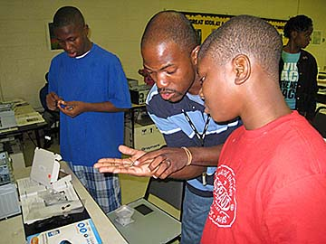 Cornelius Hamilton assists TechBridge Summer camp participant in identifying parts for the computer building project.