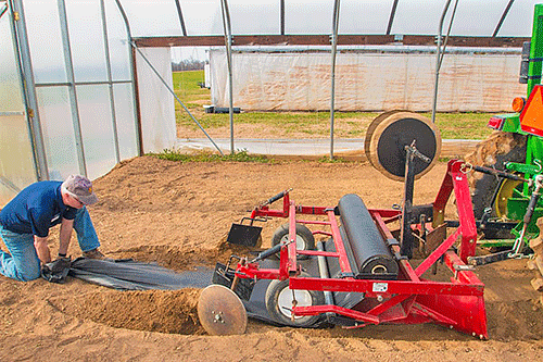 Laying plastic in a high tunnel in North Carolina. Extension at North Carolina A&T offers a plasticulture rental program that allows small farmers to try plasticulture without buying expensive equipment.