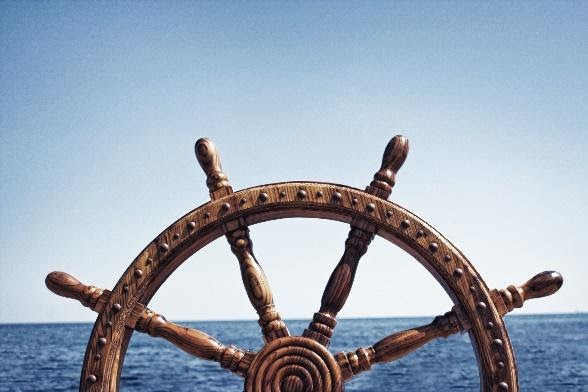 Ship's wheel with ocean water in the background.